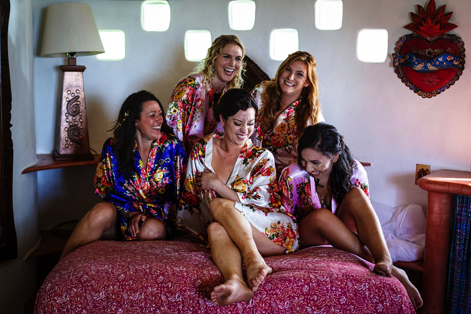 Bride and bridesmaids wearing robes on the bed of the main room at Casa Rana Verde in Sayulita