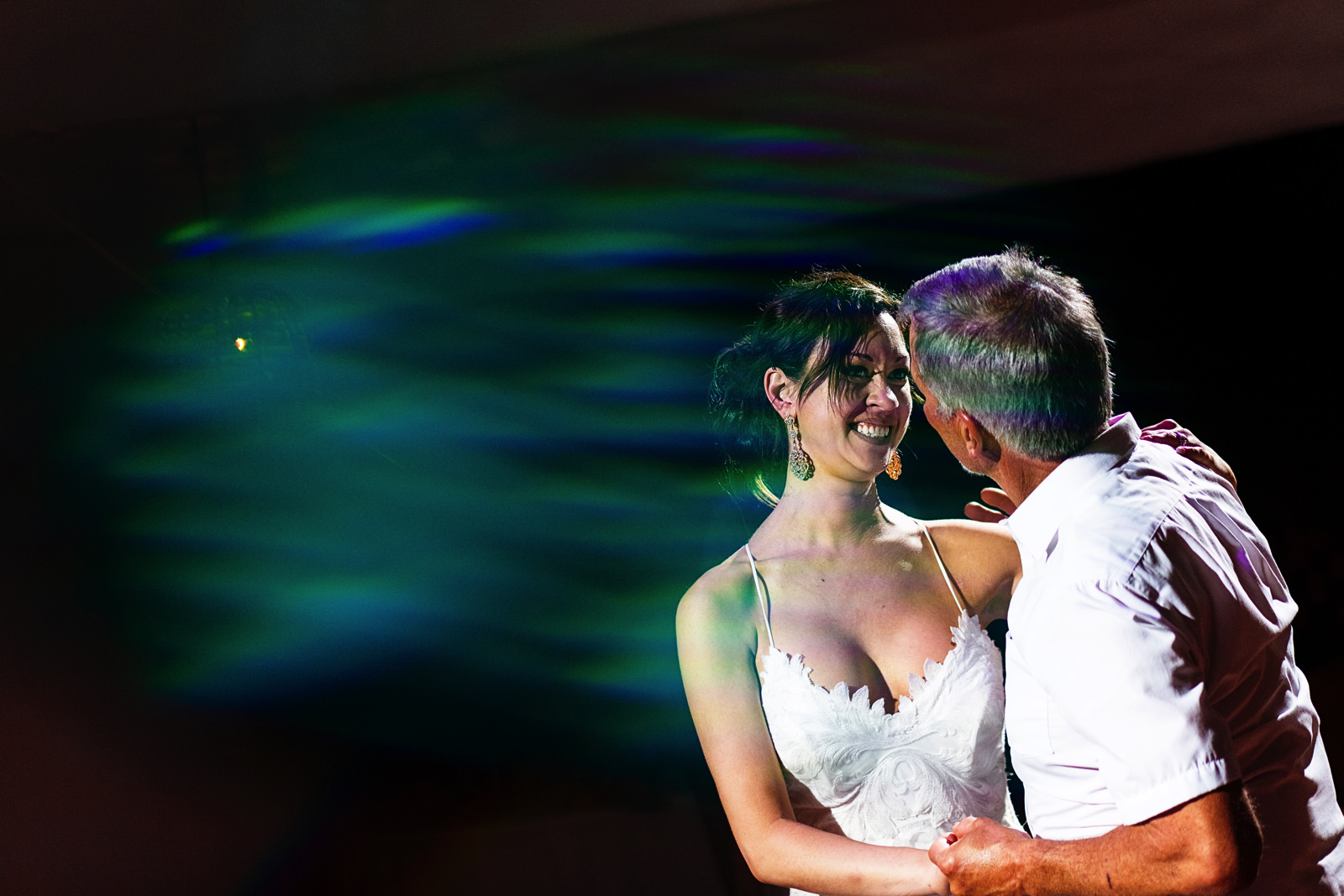 Bride and father dance with a green lens flare