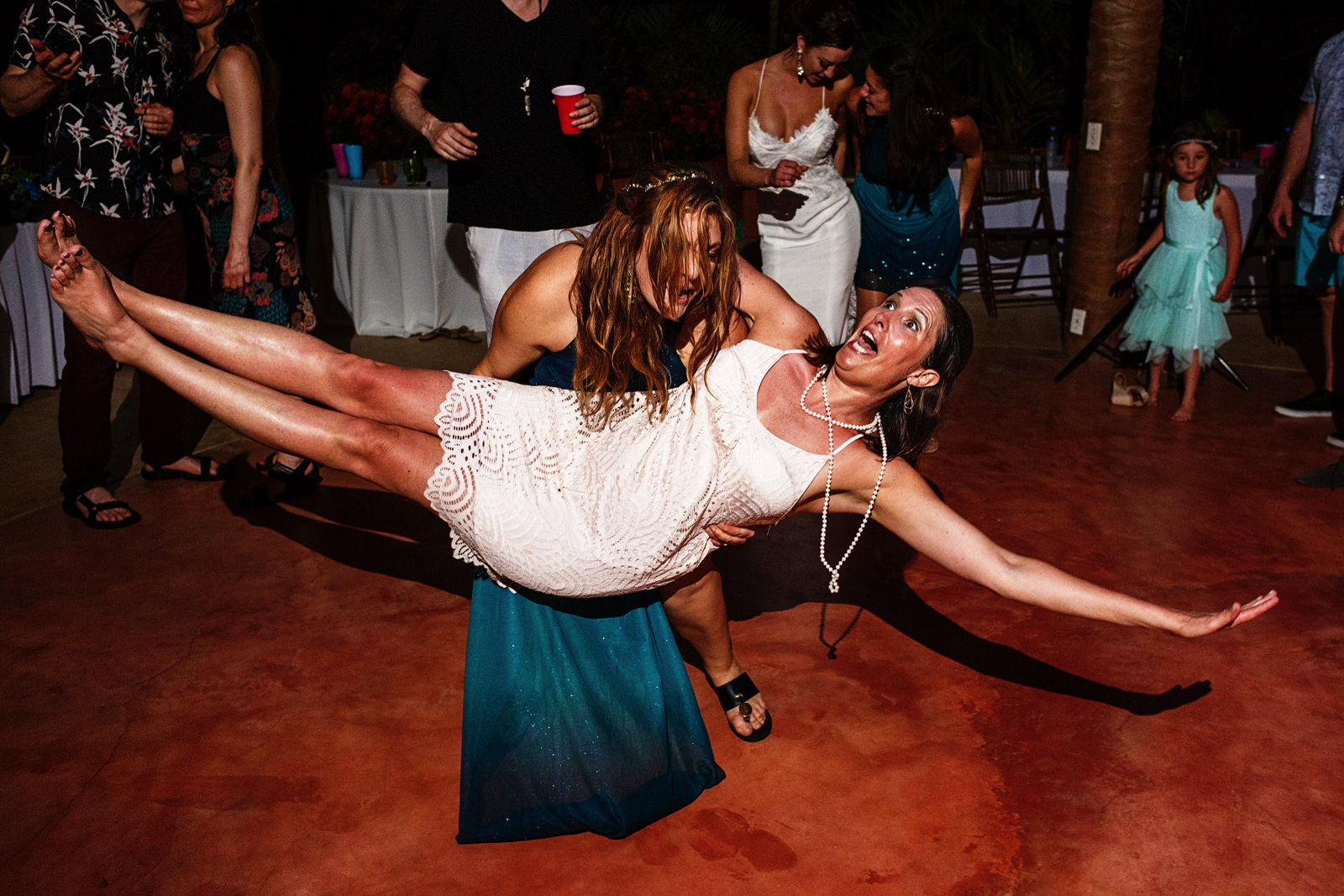 bridesmaid carries a female wedding guest in the dance floor a the party