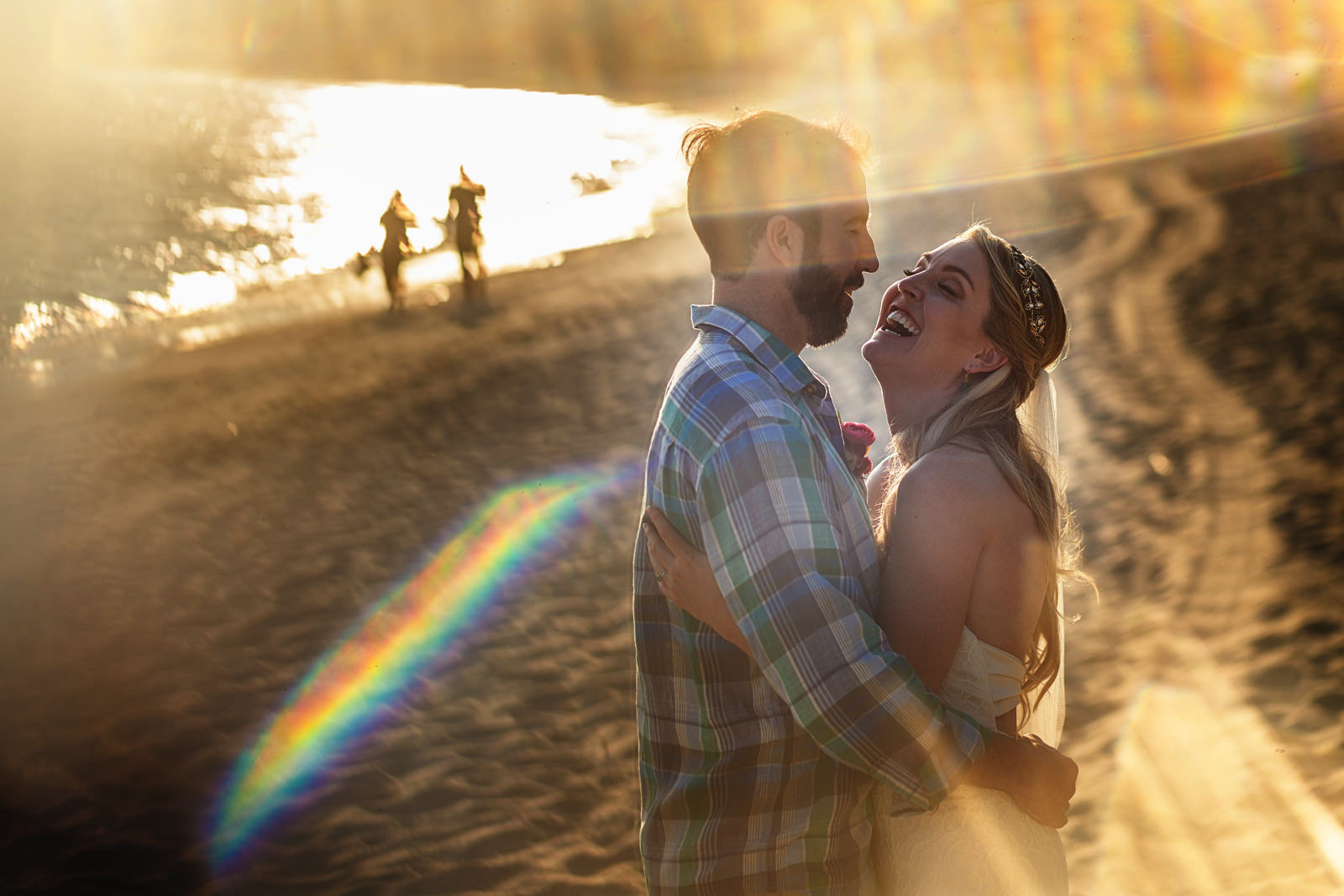 Bride and groom standing on the beach during the sunset through a lens flare.