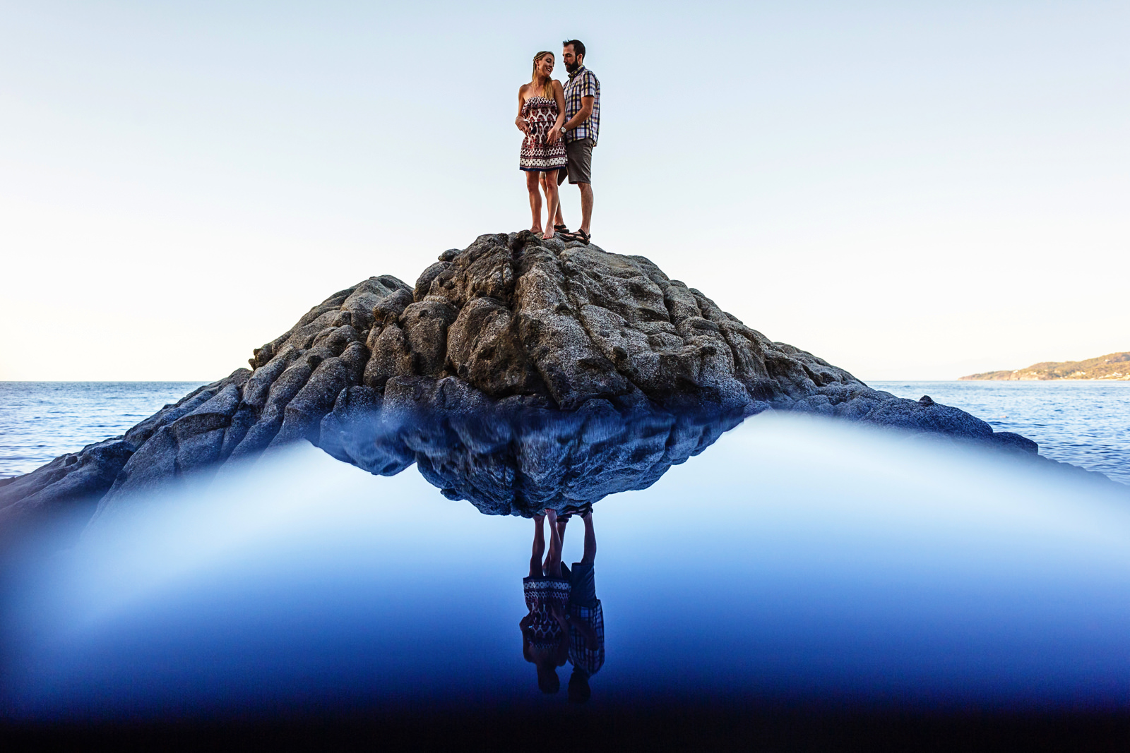 Married couple on the top of a tall rock near the pacific ocean at Playa Los Muertos, in Sayulita.