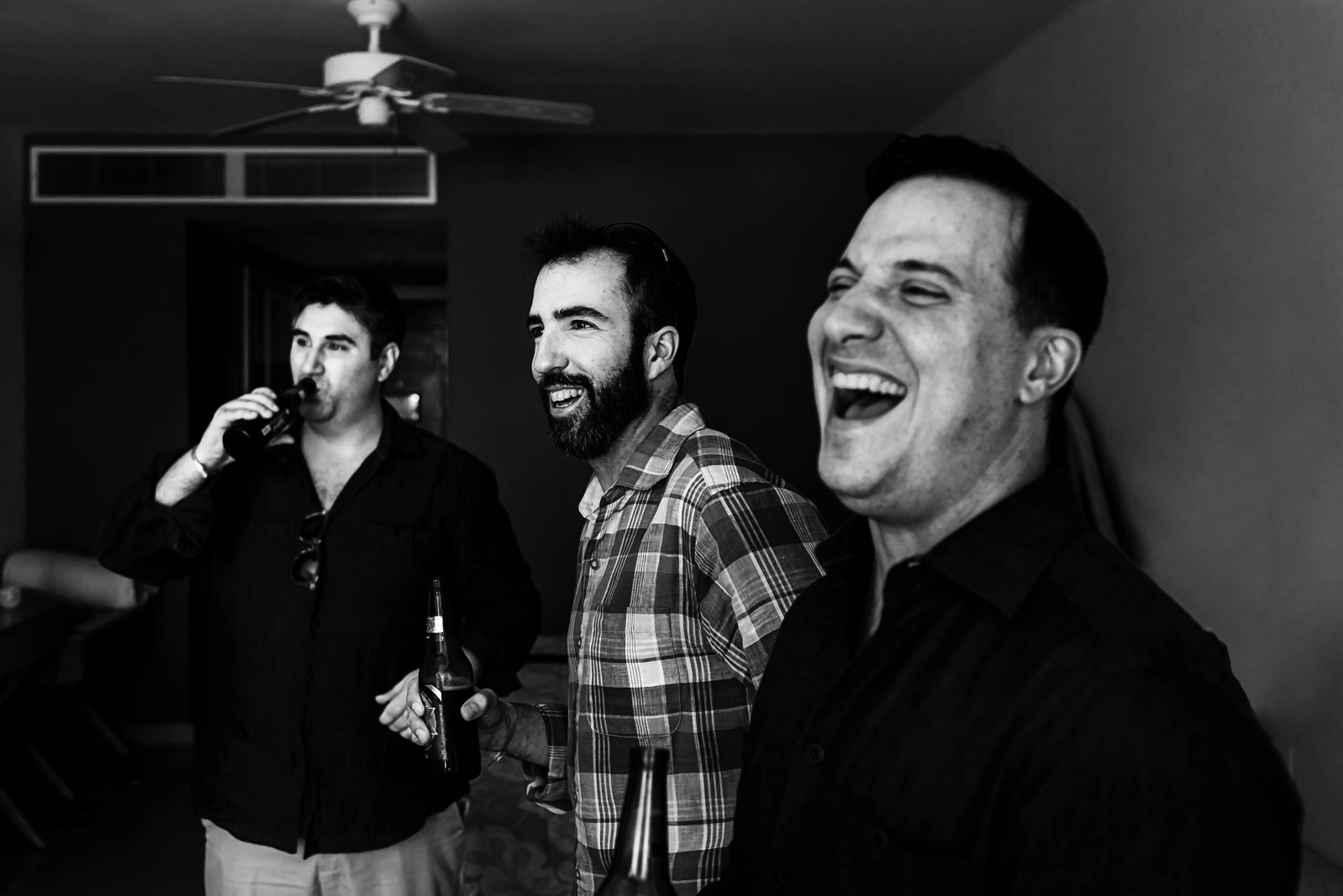 Groom and groomsmen enjoying beers and sharing a laugh at an Iberostar Punta Mita room