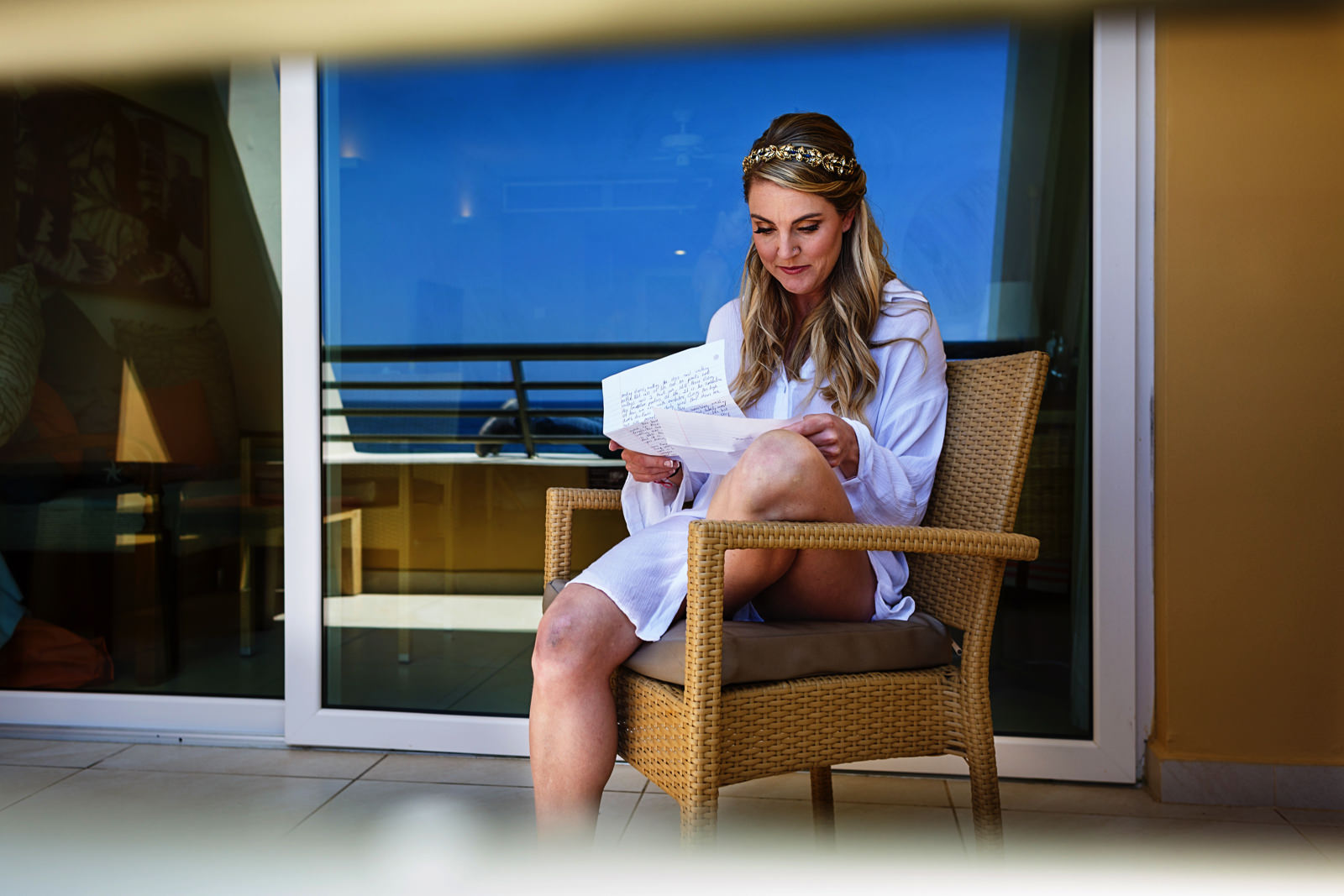 Bride reading groom's letter to her at the balcony of an Iberostar Punta Mita room
