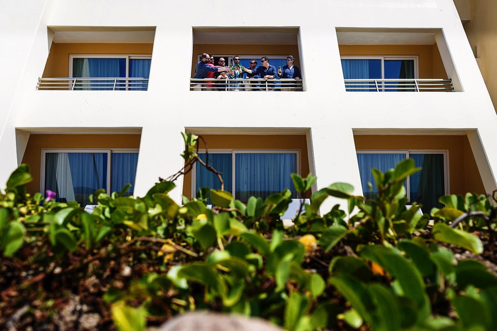 Groom and groomsmen clinging beers at an Iberostar Punta Mita room's balcony