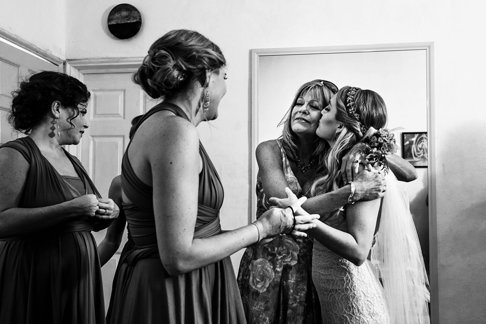 Bride and mother hug and kiss at the Martoca's bridal suite before the wedding ceremony