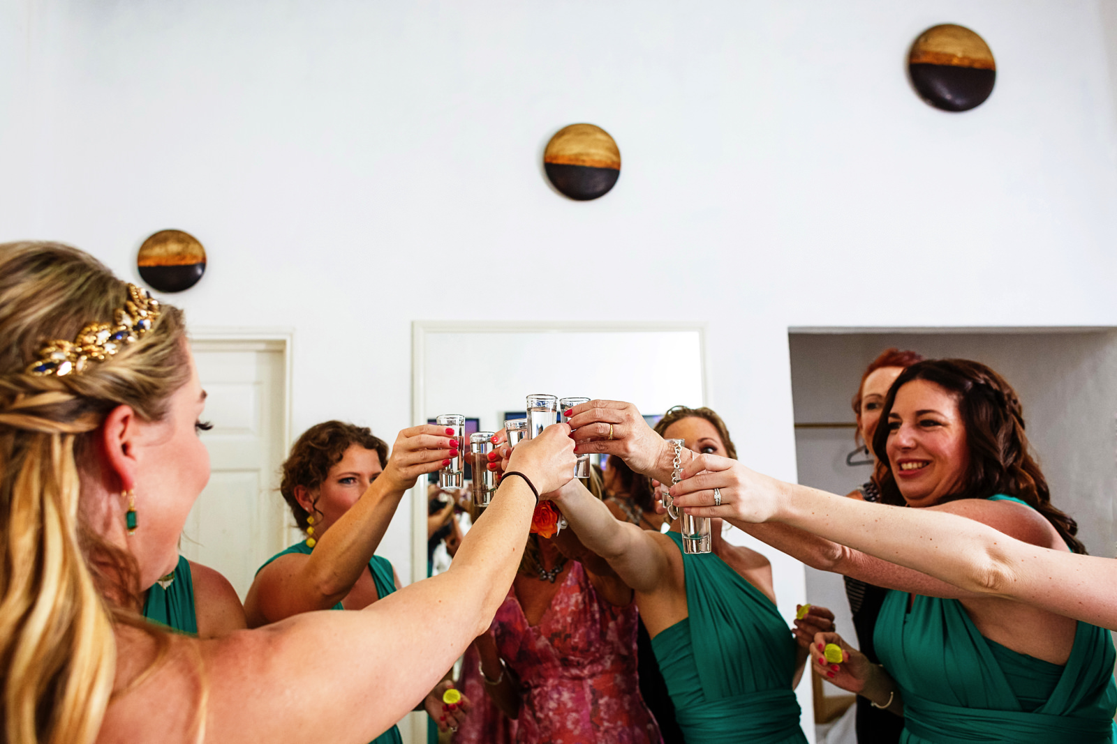 Bride and bridesmaids toast with tequila shots at the Martoca's bridal suite before the wedding ceremony