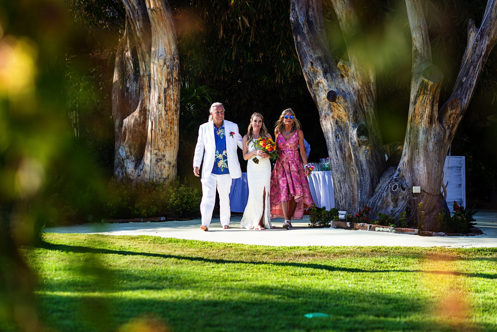 Bride walking to the aisle of the wedding ceremony with her mother and father