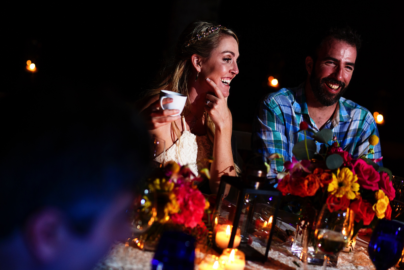 Bride and groom laugh during wedding dinner speeches