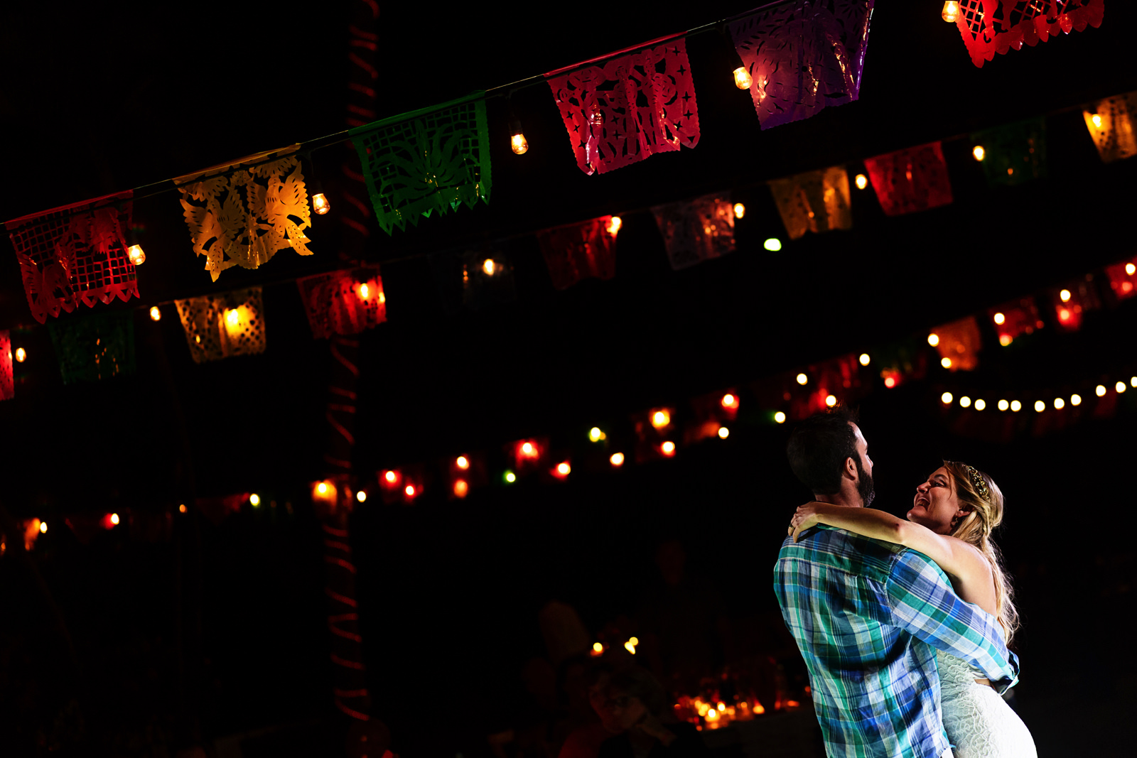 Bride and groom first dance under papel picado decoration