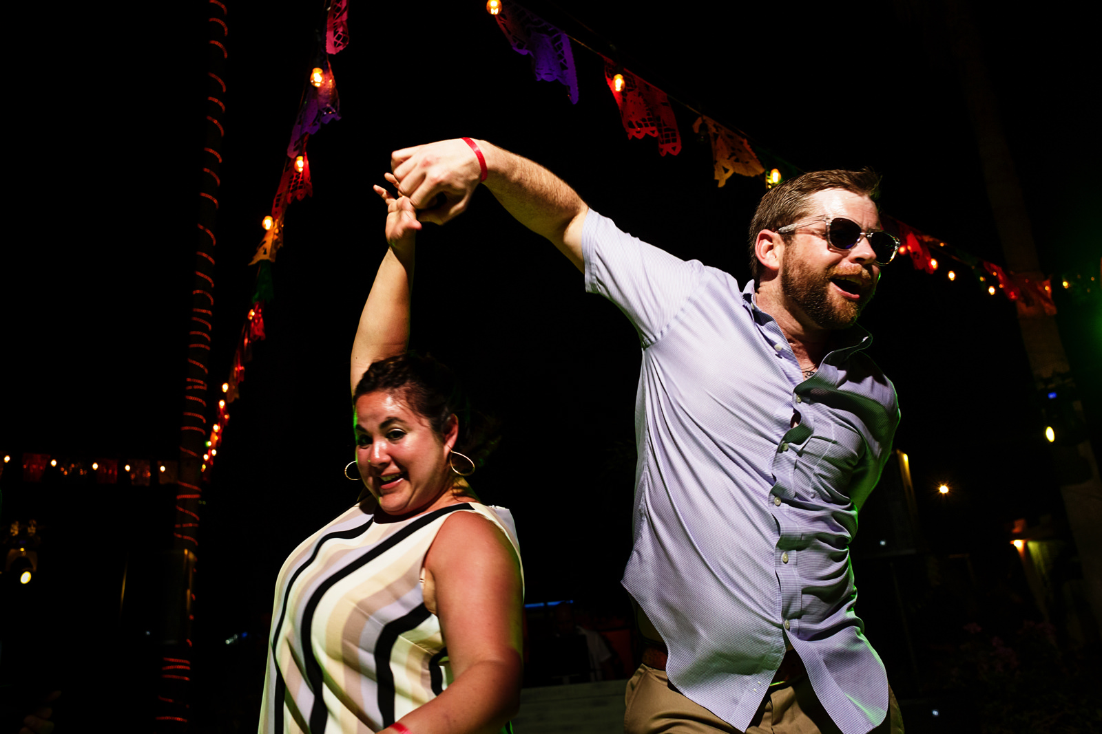 wedding guests dancing at the party with complex dance moves and spins
