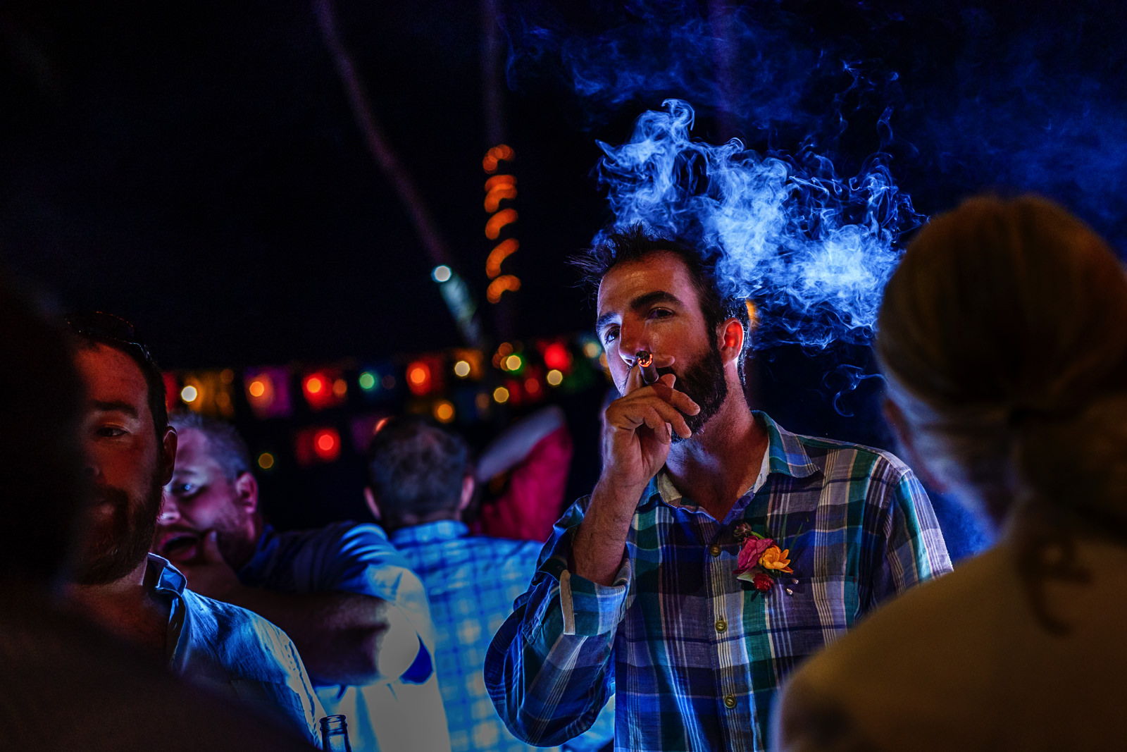 Groom smoking a cigar at the bar with friends