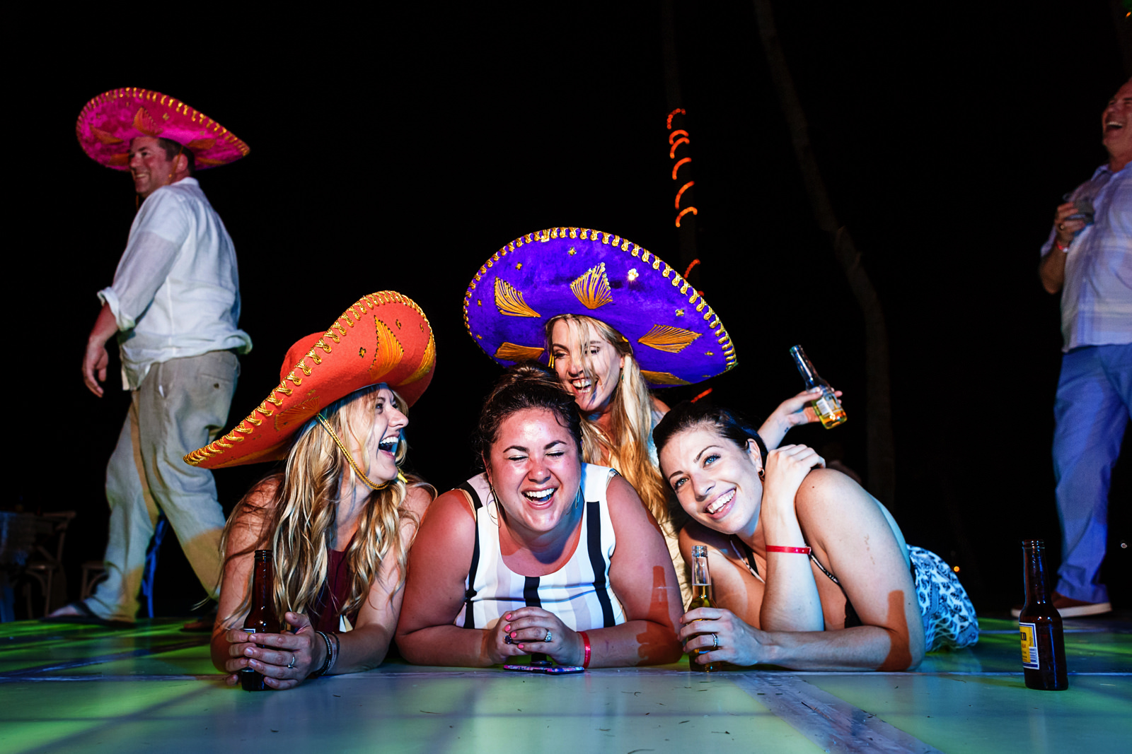 Bride and friends laying over the illuminated dance floor wearing mexican sombreros