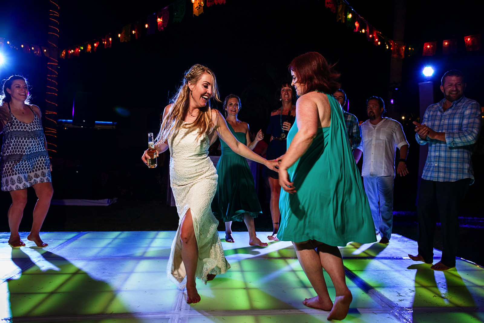 Bride and female wedding guest dancing in the middle of a circle of other guests