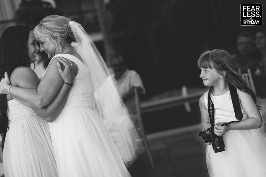 Bride and daughter dancing face to face and little girl holding a camera watching the moment at wedding reception - Fearless photo of the day