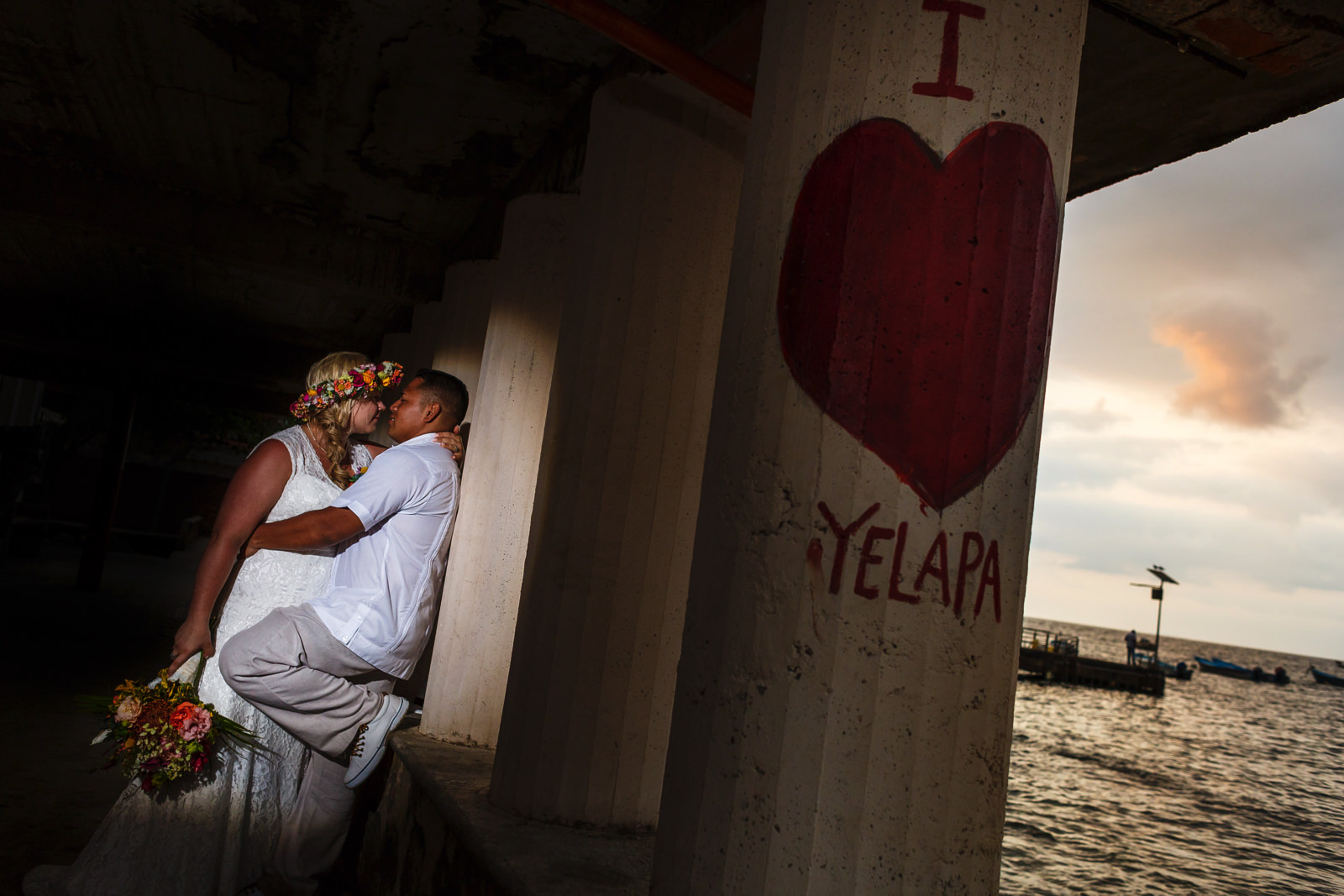 "Bride and groom leaning against a column with ""I <3 Yelapa"" painted on, and the sun setting in the background."