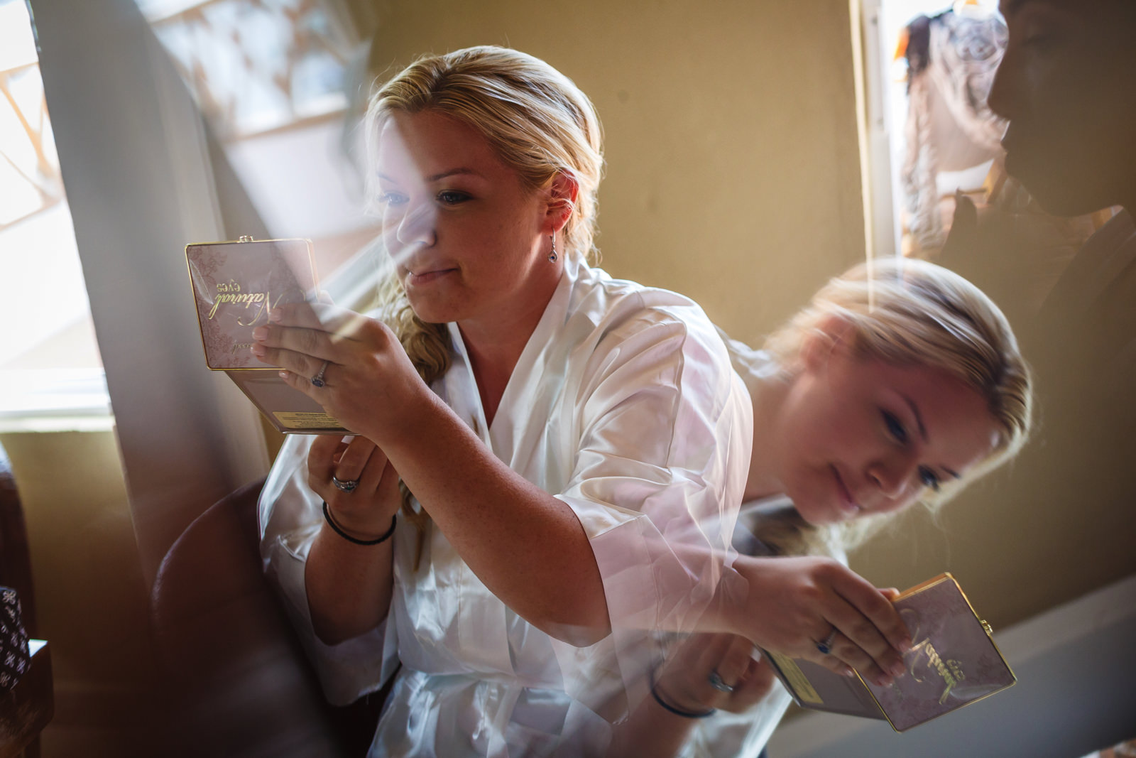 Bride looking at herself on a hand mirror all pretty and almost ready for the wedding ceremony.