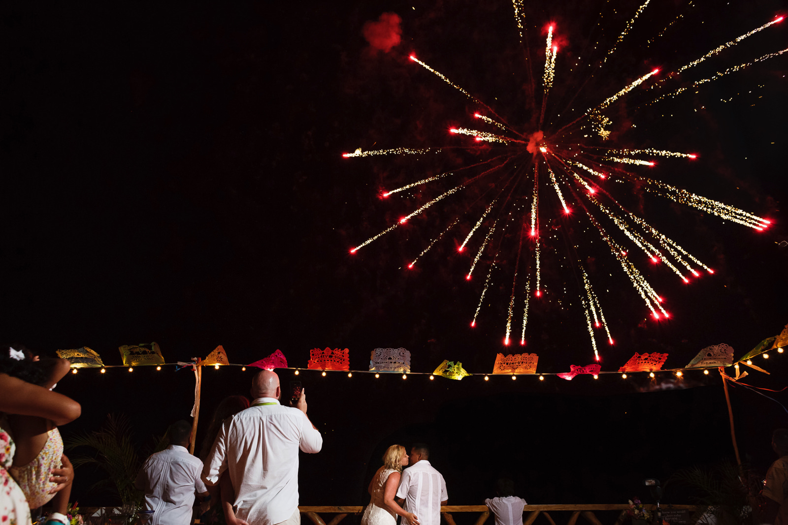 Fireworks exploding near the Miramar terrace while the bride and groom kiss.