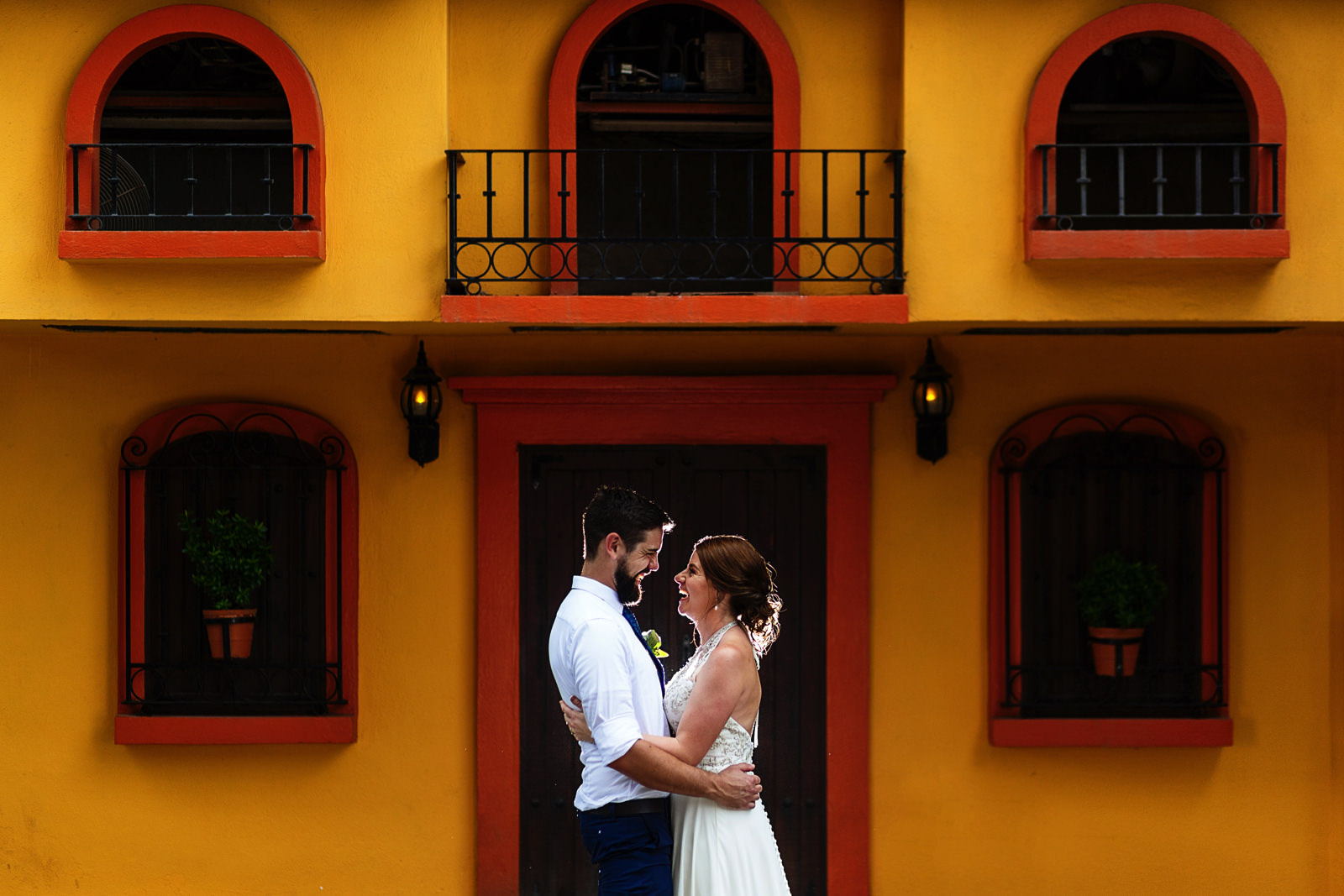 Bride and groom laughing facing each other outside a Mexican styled facade.