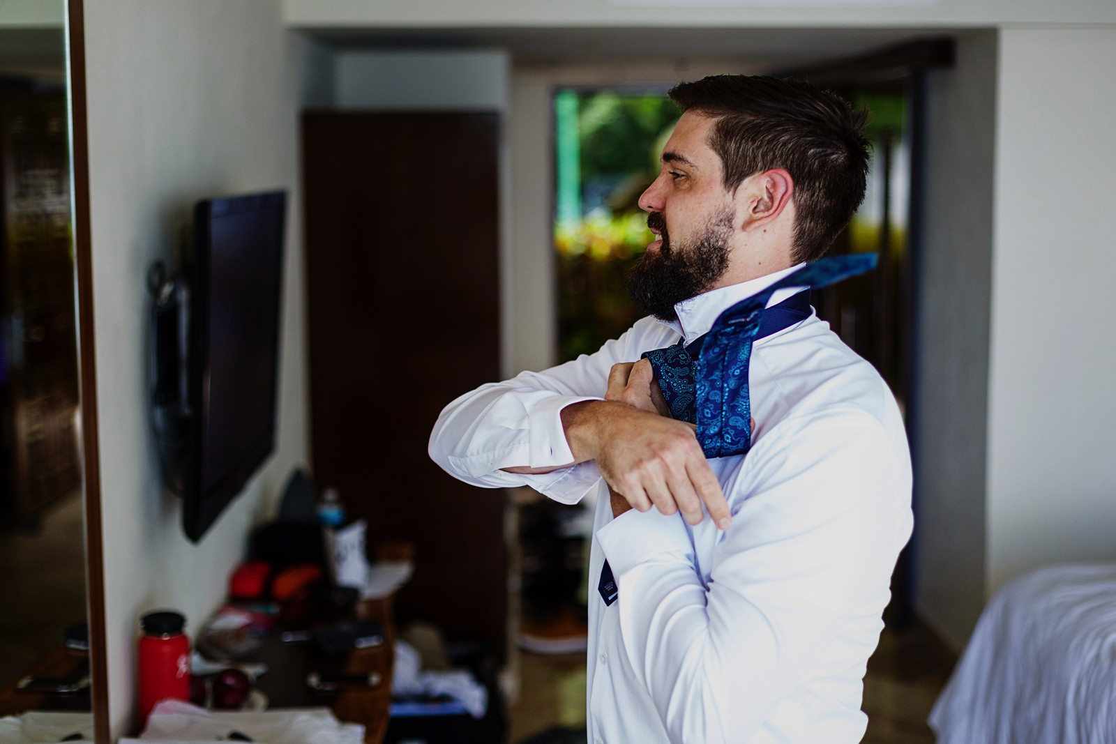 Groom looking at himself in the mirror while doing his tie knot.