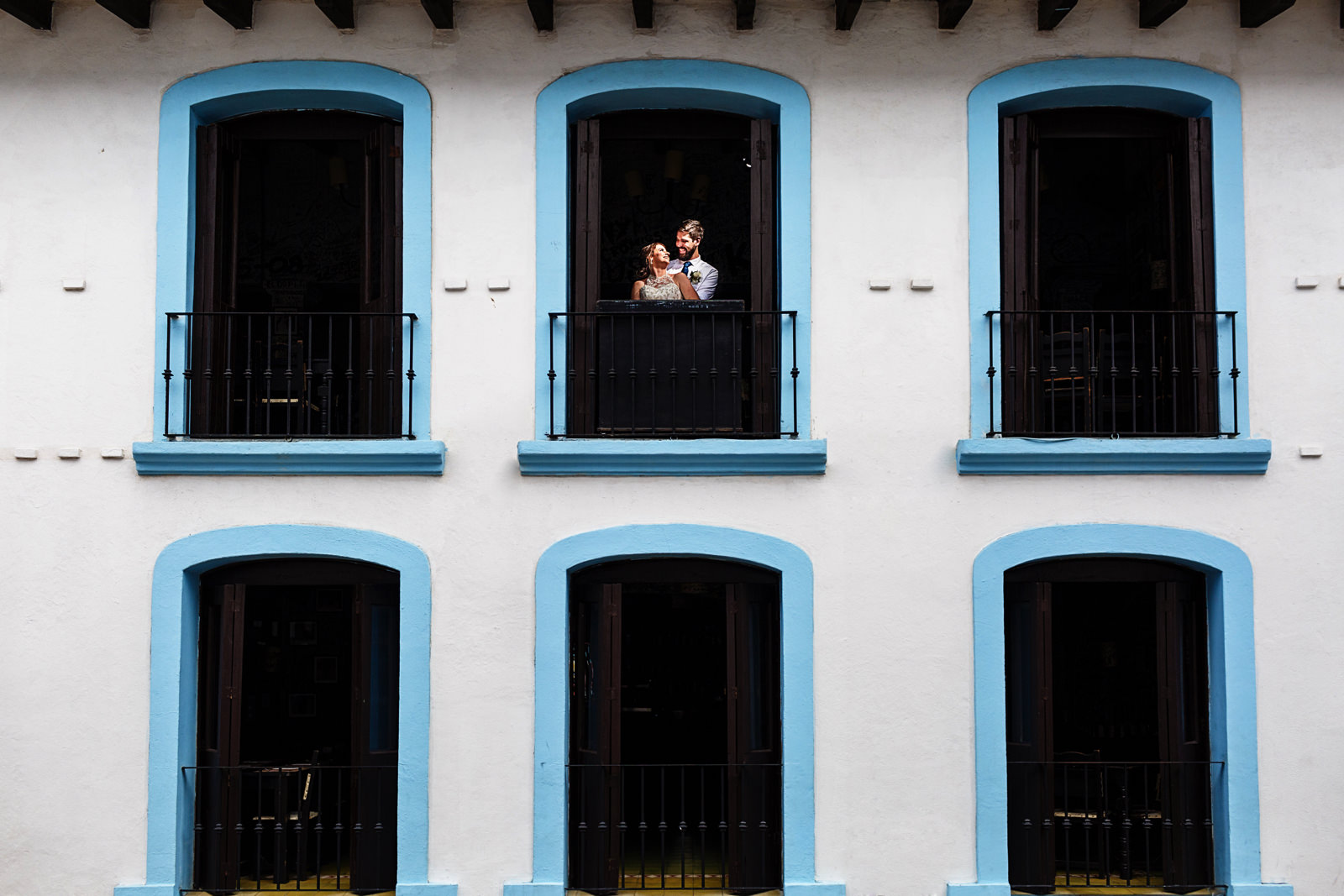 Groom and bride portrait, the couple is framed on a blue window with a white facade.