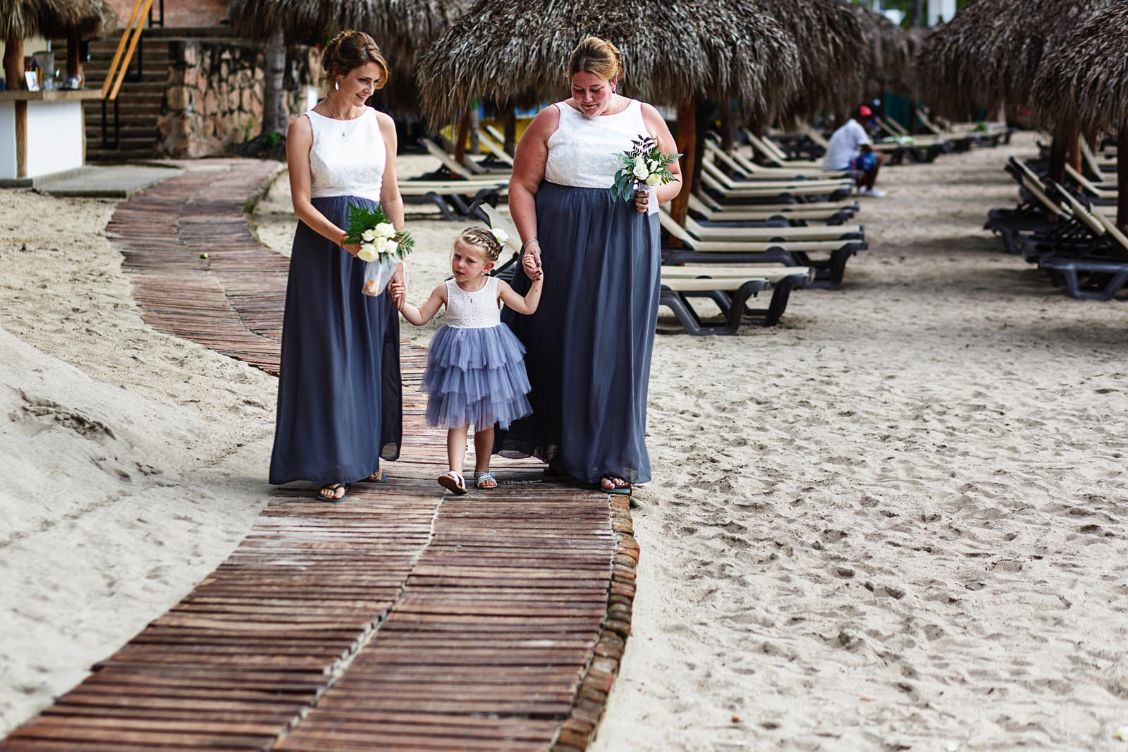 Bridesmaids and flower girl walking down a wood path on the beach for the wedding ceremony to start.