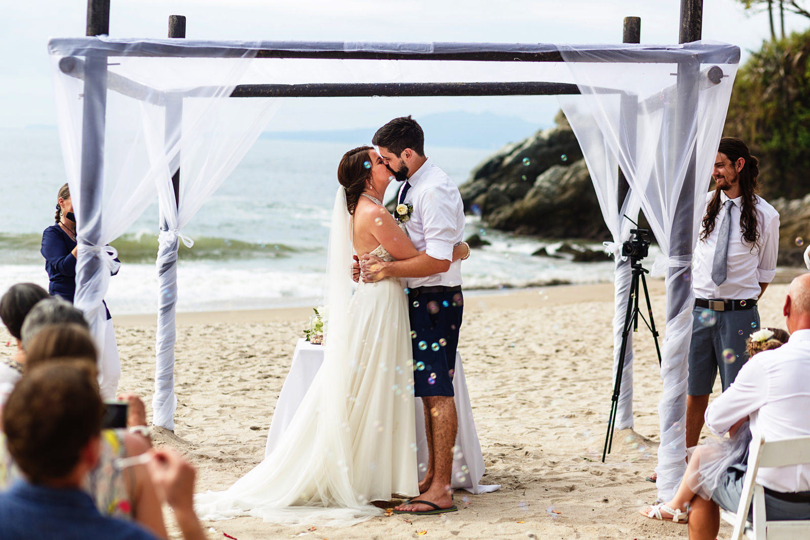 Bride and groom first kiss while the wedding guests blow bubbles at the end of their beach wedding ceremony.
