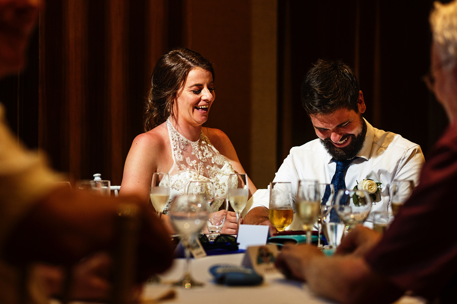Groom and bride laughing during the speeches at the dinner table.
