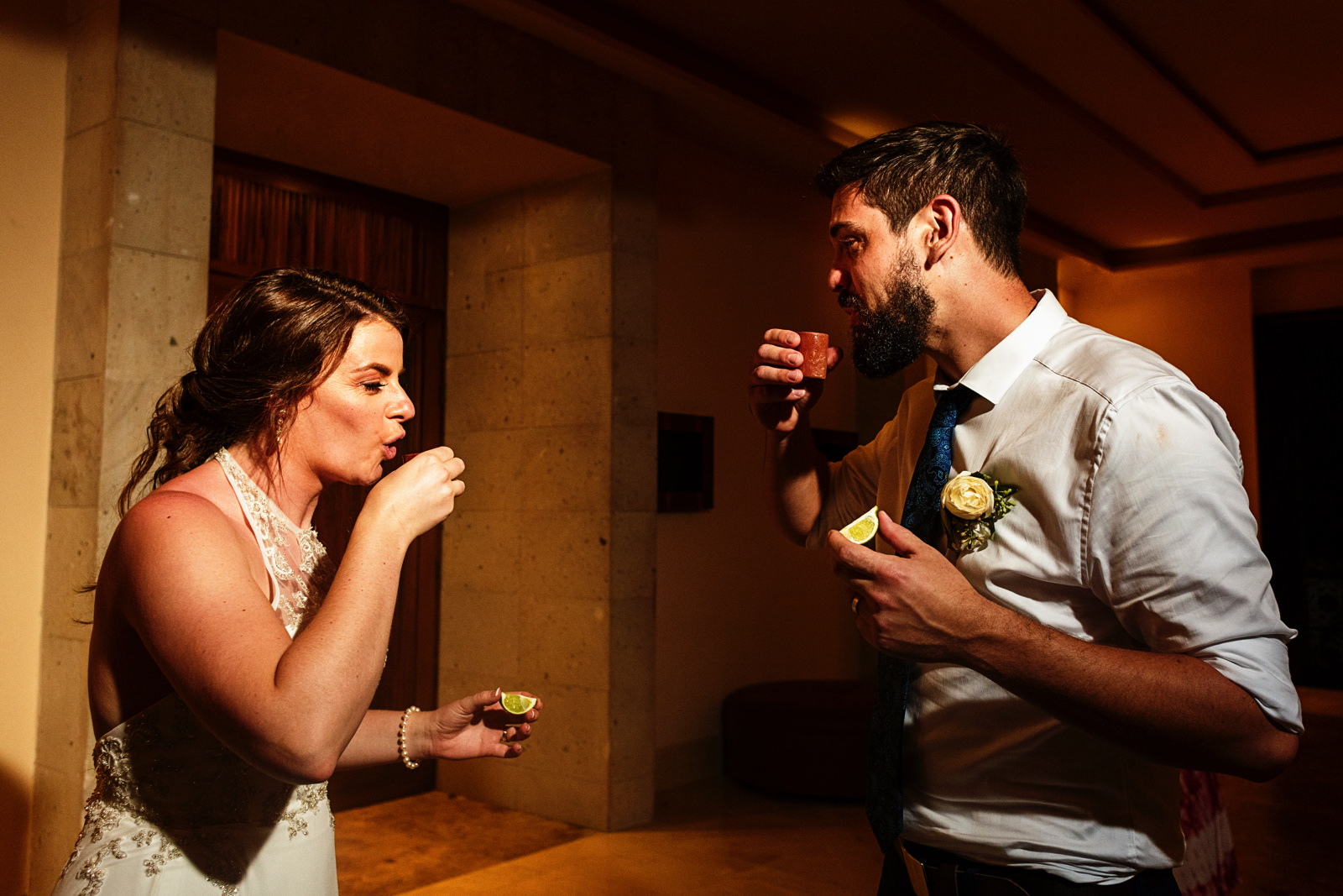 Groom and bride about to drink a tequila shot, while holding  a slice of lime on the other hand.
