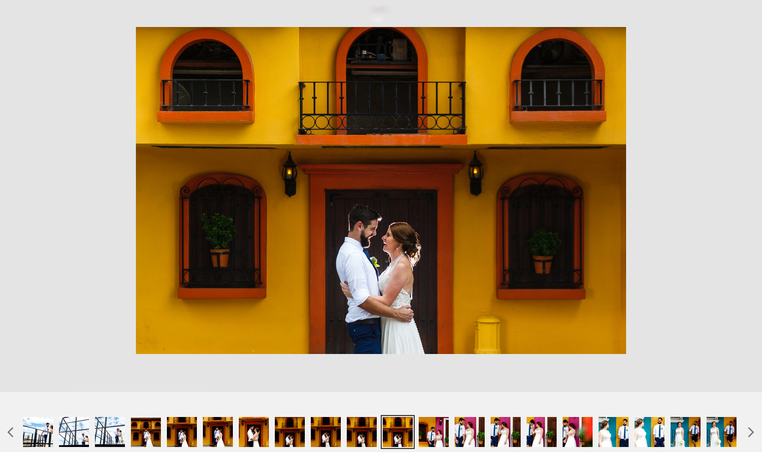 Groom and bride laughing at each other outside a yellow Mexican style facade.