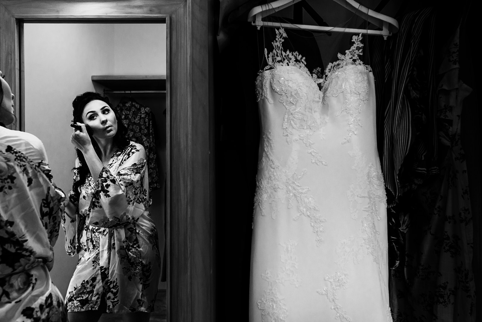 Bride doing her make-up right next to her wedding dress.