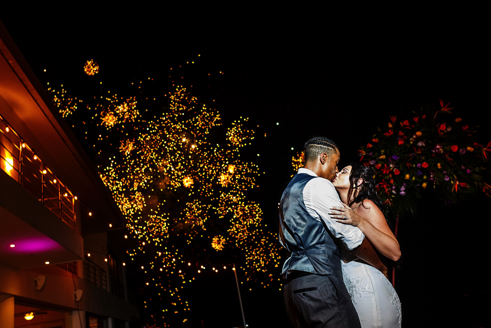 Fireworks explode in the background as the bride and groom kiss at the ned of their first dance.