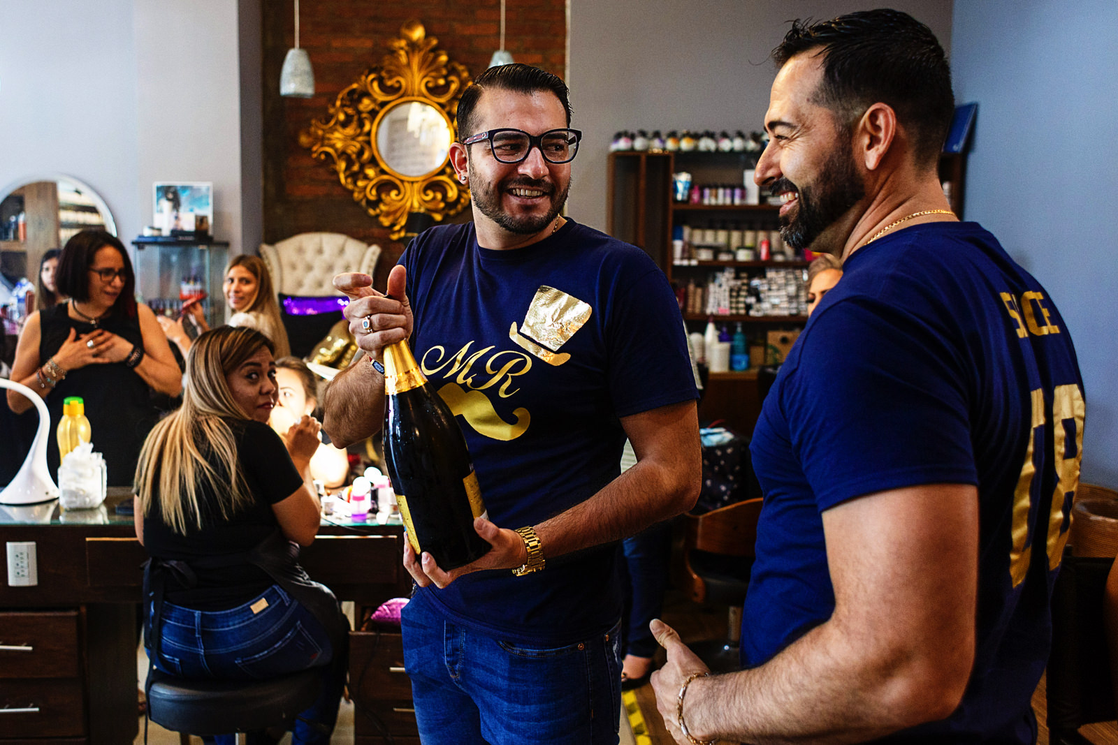 Gay couple opening a bottle of champagne during the getting ready of their wedding, at their beauty salon.