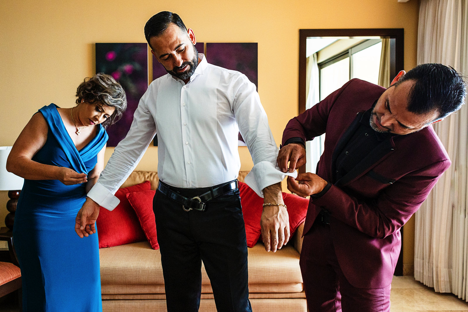 Groom is helped by godparents to put on the cufflinks.