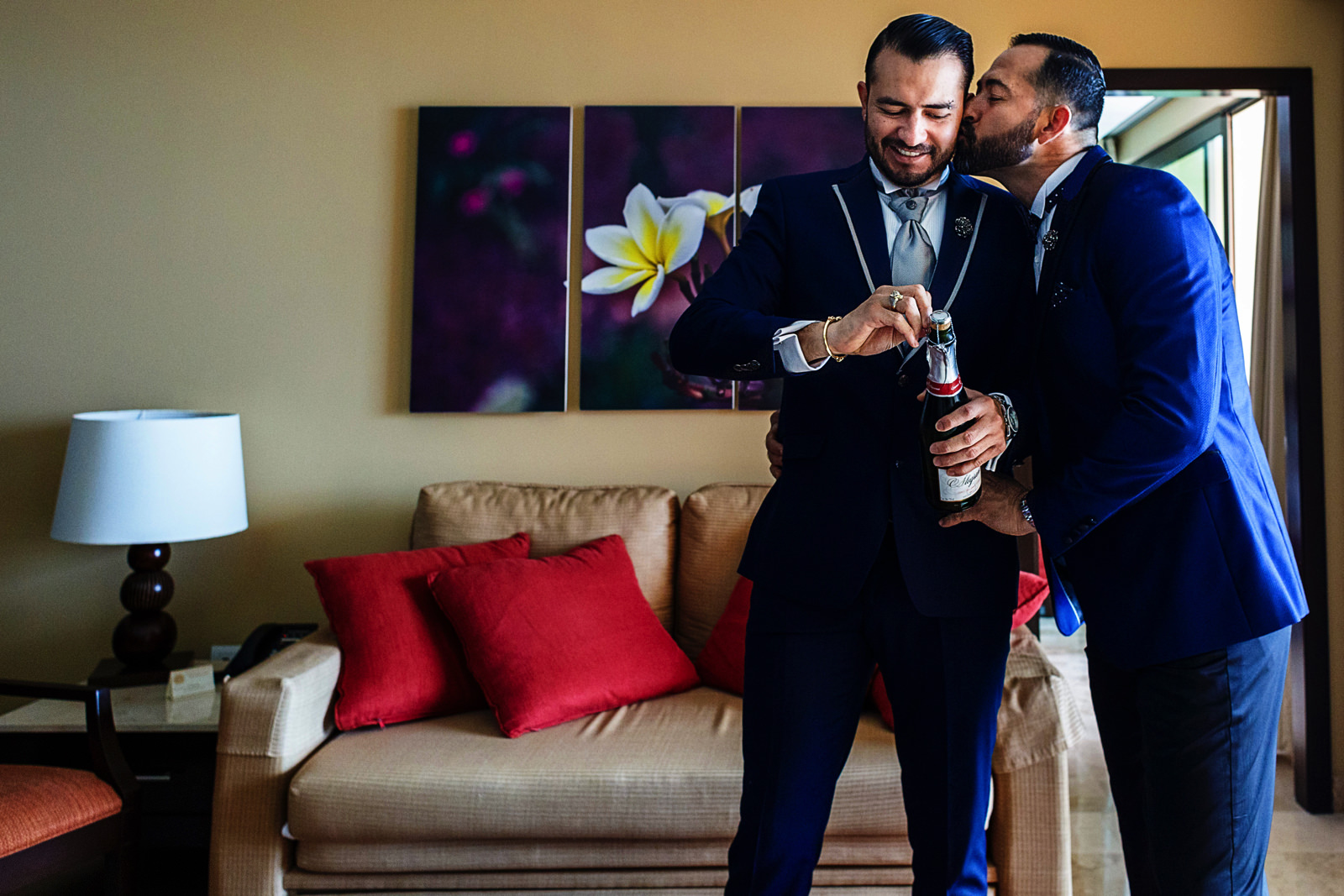 Gay couple opening a bottle of champagne all dressed up on tuxedos before their wedding ceremony.