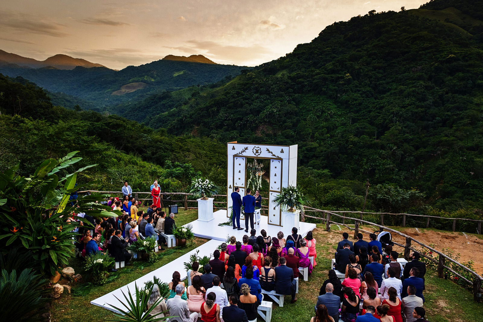 Gay couple at their wedding ceremony on top of the mountain surrounded by the Sierra Madre.