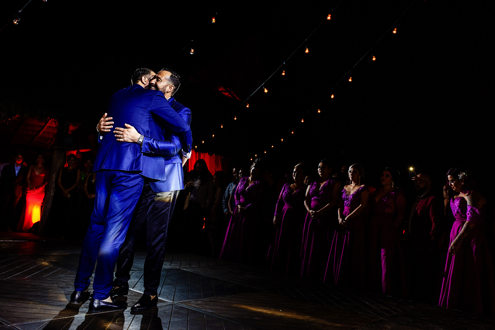 Gay couple on their first dance surrounded by friends and family.