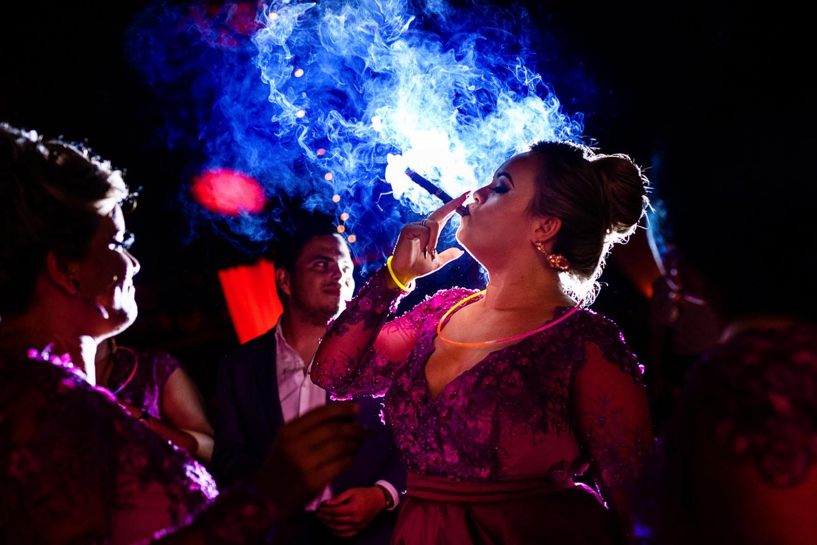 Groomsmaid smoking a cigar at the party.