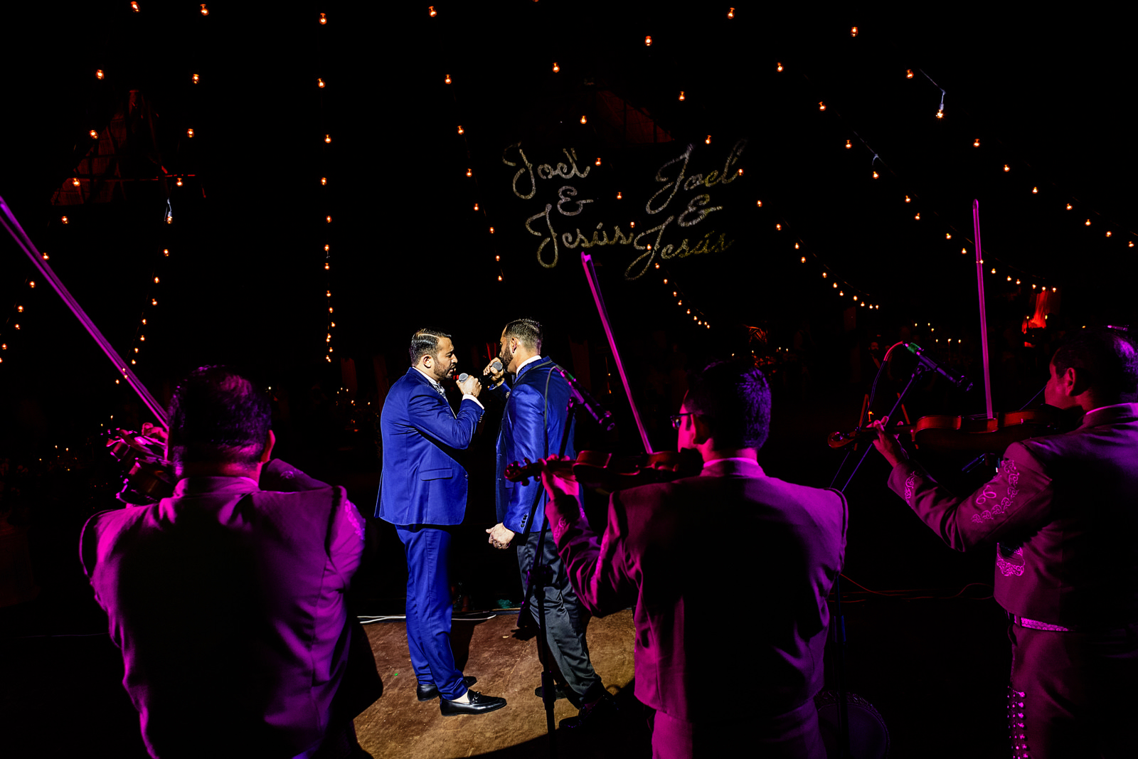 Gay couple of grooms singing on the stage with the mariachi band playing behind them.