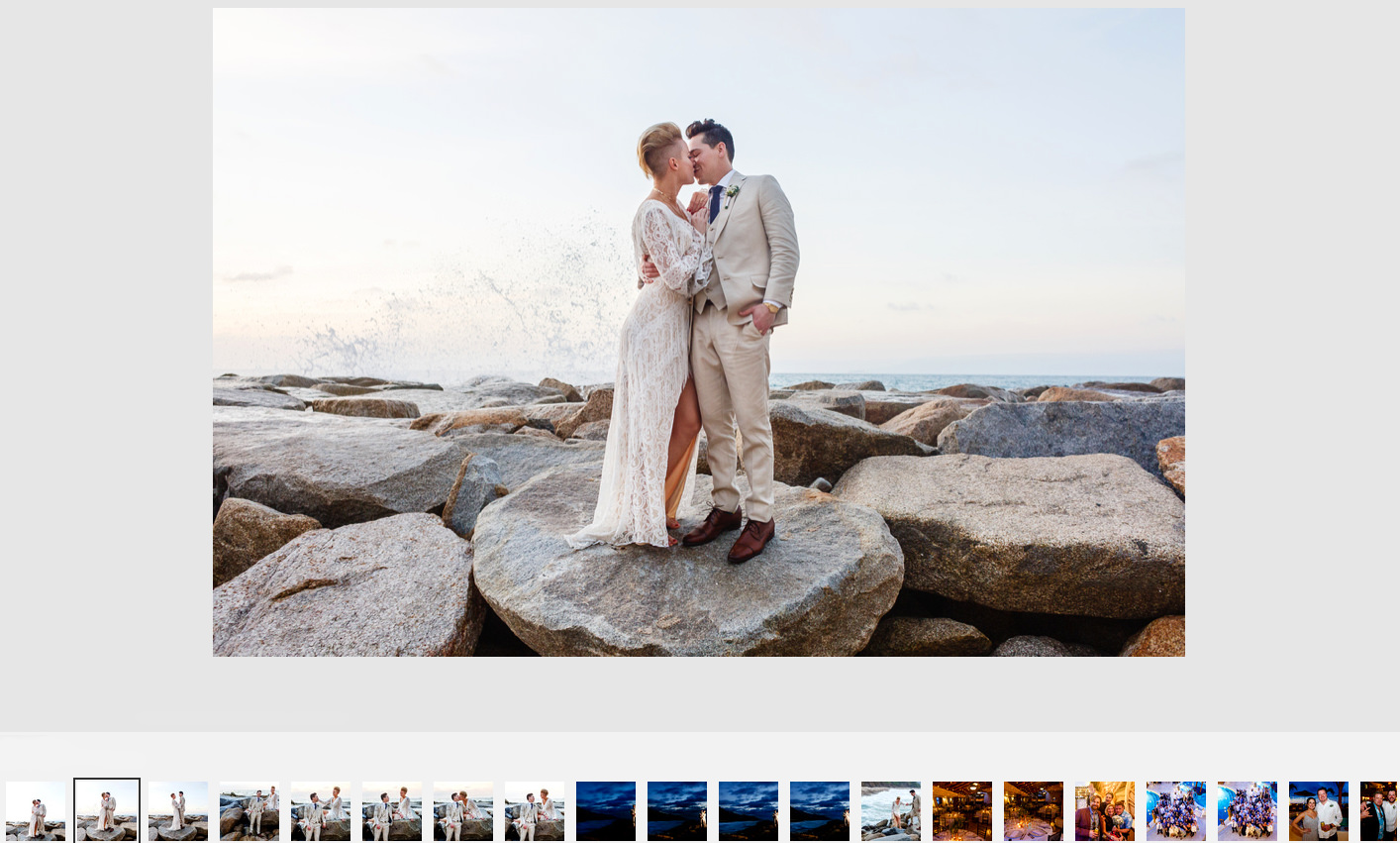 Bride and groom kissing as a wave crashes behind them, at Hotel Playa Fiesta south of Puerto Vallarta, Mexico.