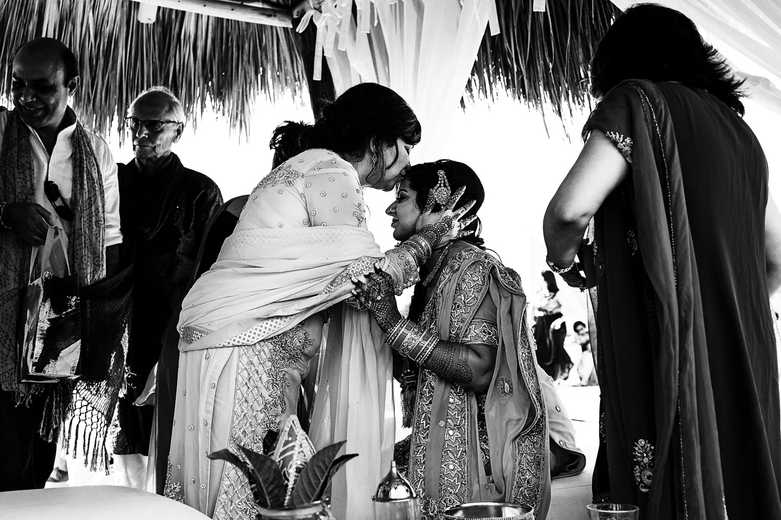 Mother of the bride kiss her forehead at the end of a hindu ceremony