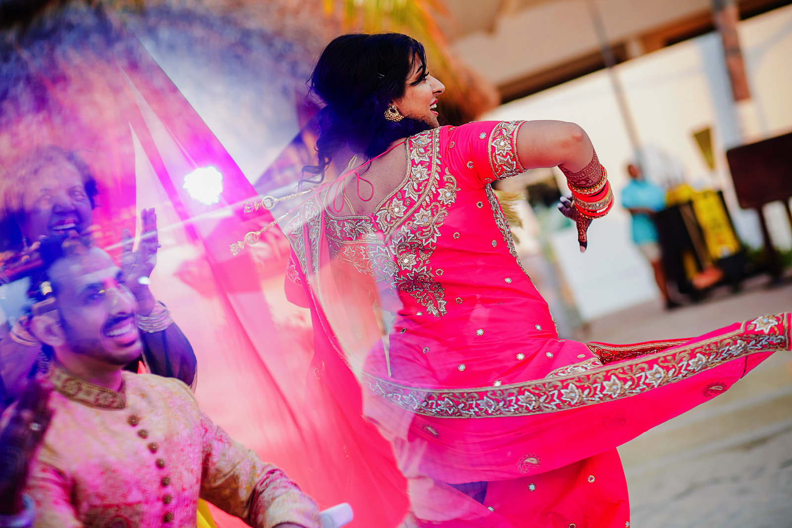 Hindu bride performs and groom is seen through a mirror reflection