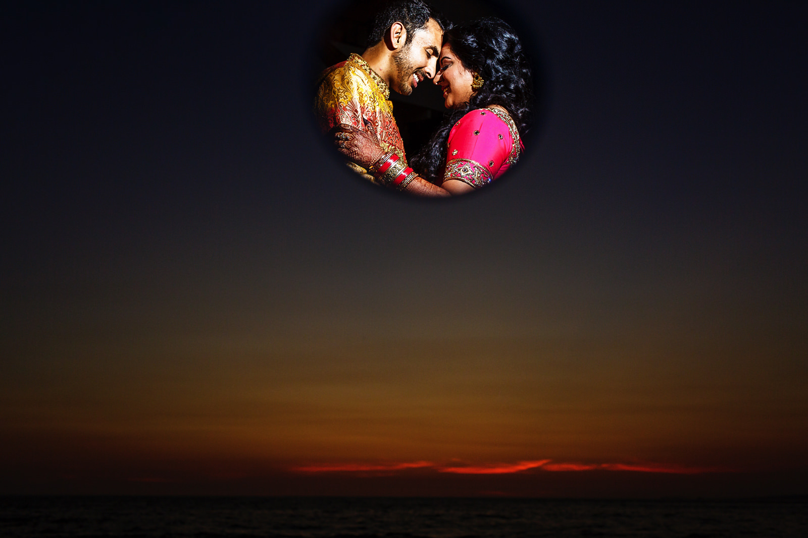 Hindu wedding couple seen through a mirror against the sunset colors and the ocean.