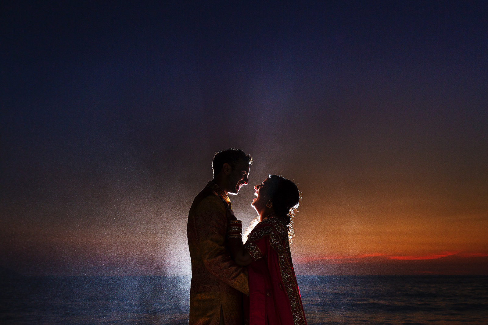 Portrait of hindu groom and bride with backlight against the sunset colors