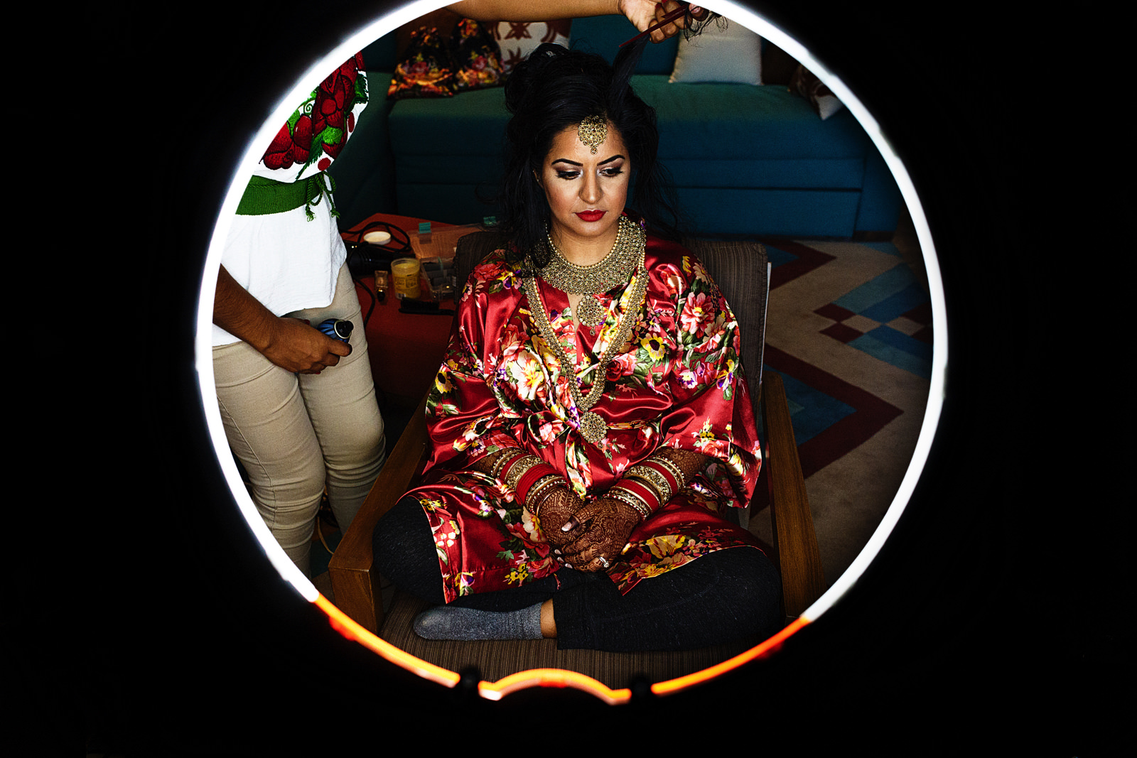 Hindu bride getting her hair done seen through a ring light