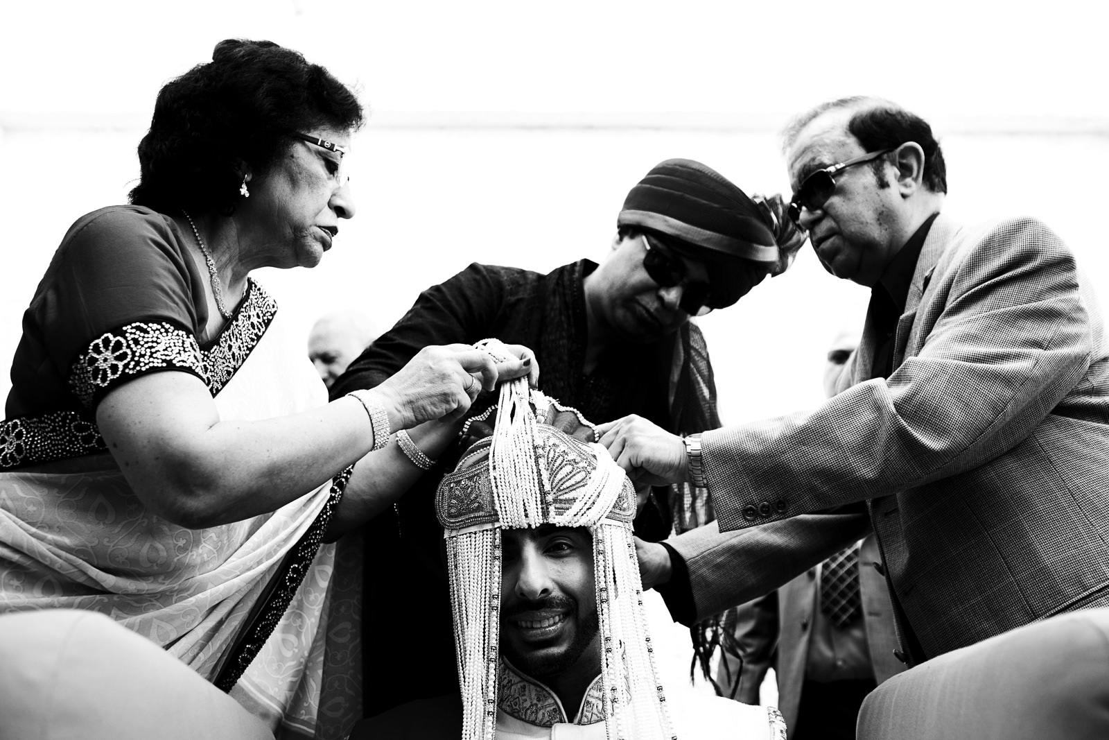 Family of the groom help him with hindu traditional hat before the wedding ceremony