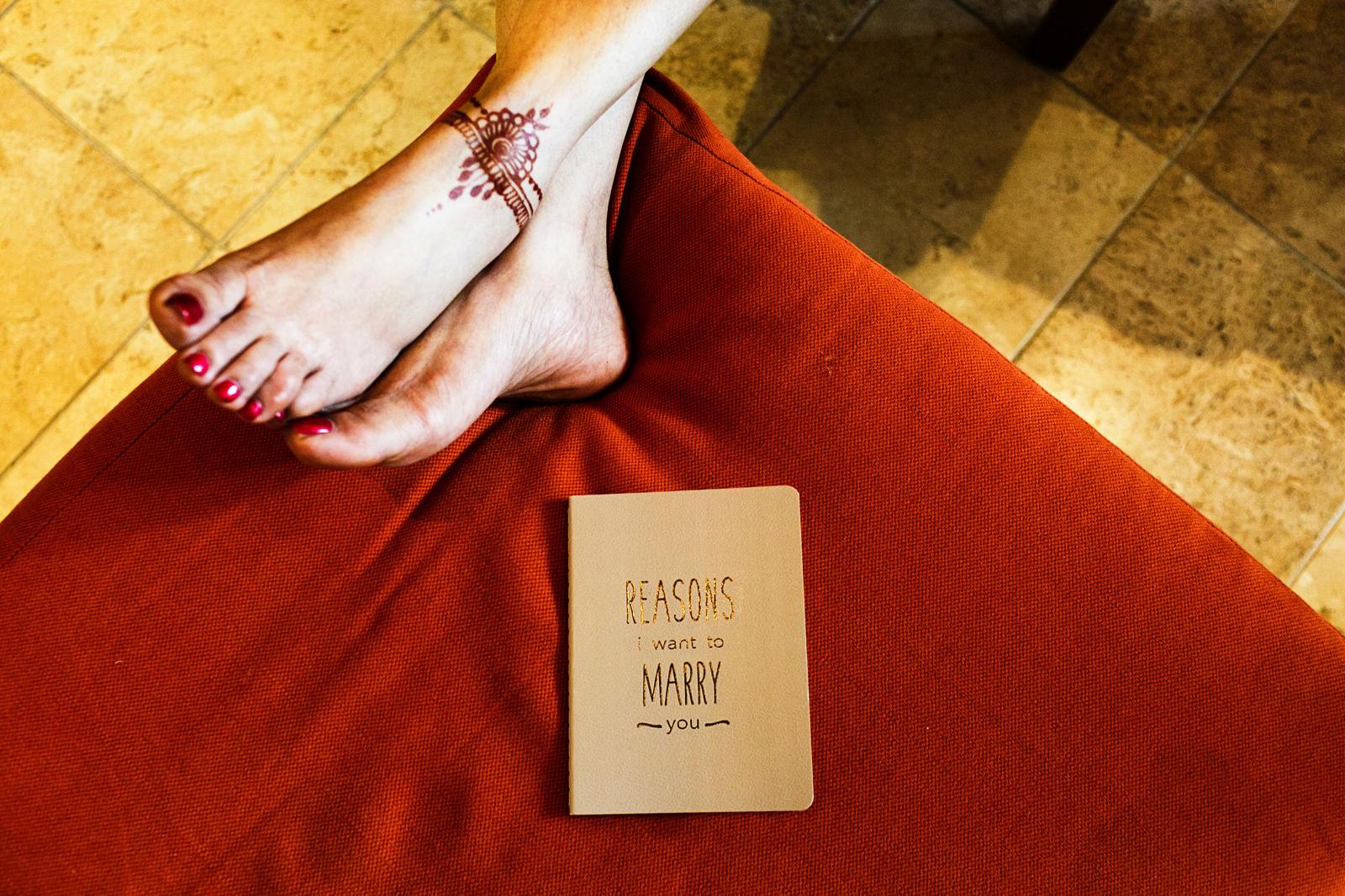 Wedding detail vows book next to henna tattooed bride's feet