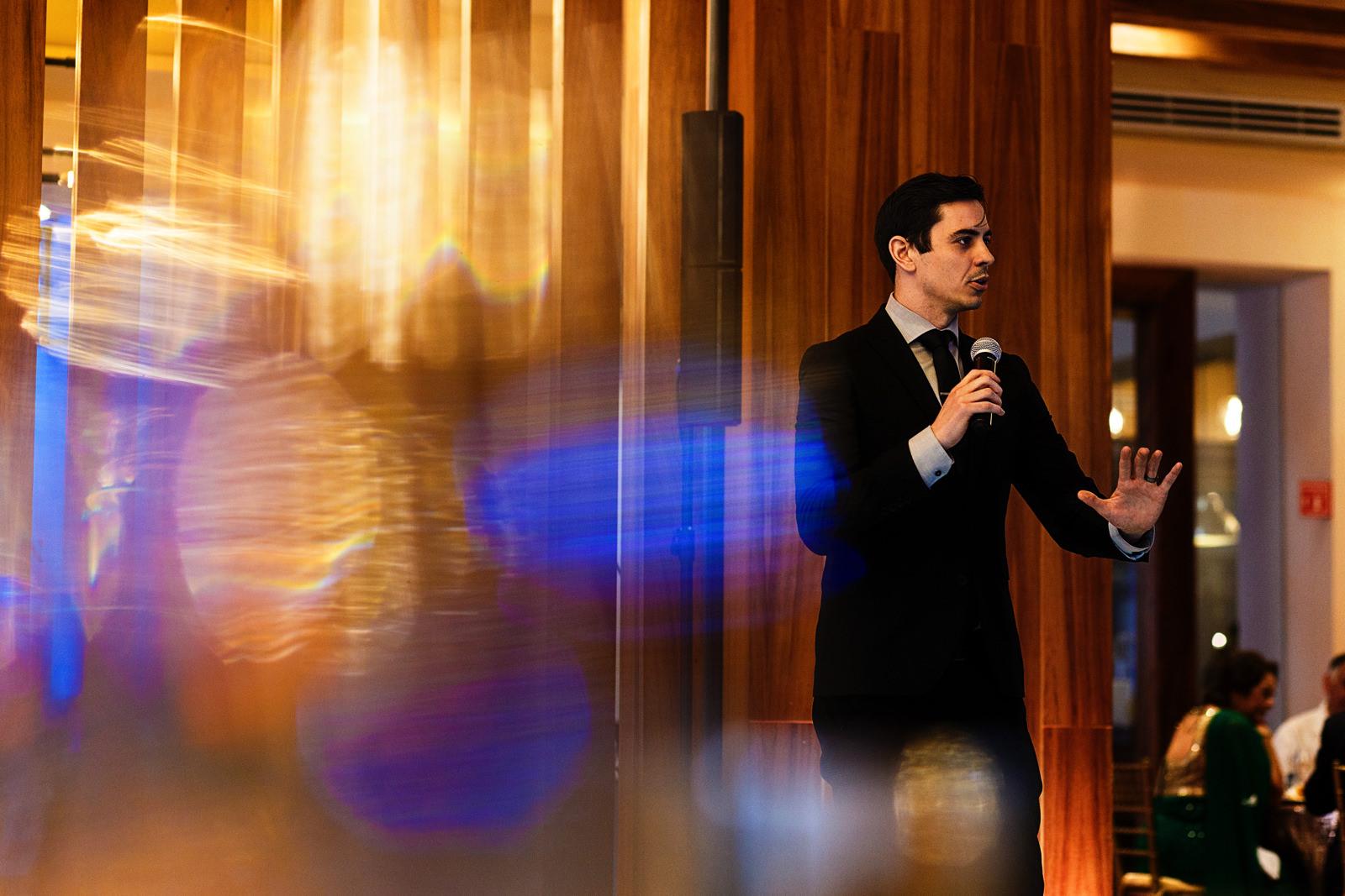 A man gives an speech at wedding reception