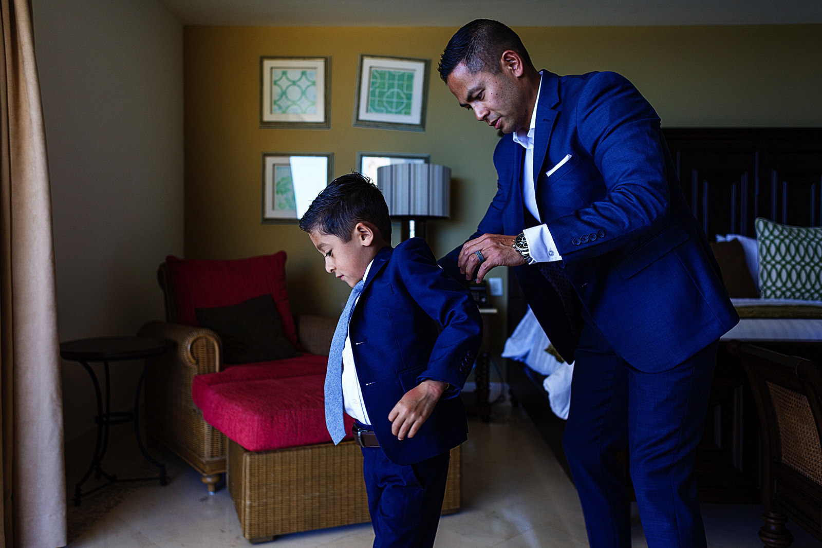 Groom helping his son to put on his suit jacket