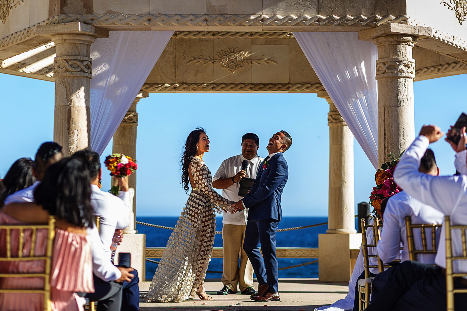 Bride and groom laughing during their destination wedding ceremony in Cabo San Lucas