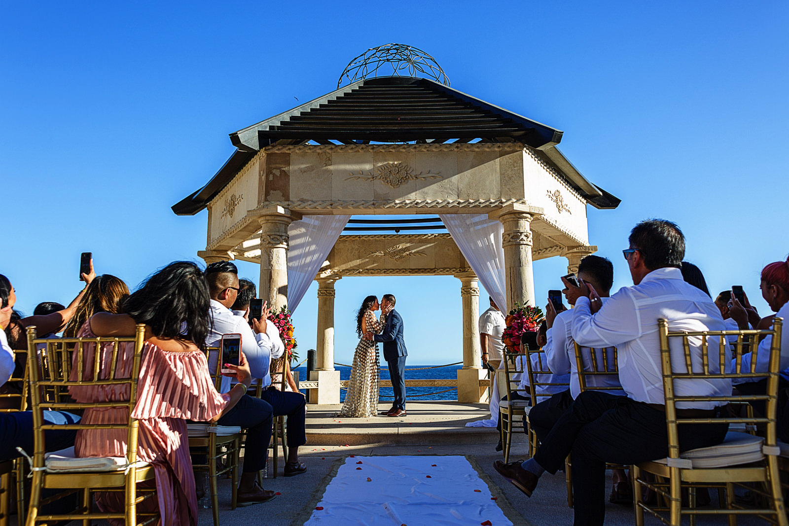 Groom and bride's first kiss at the end of the destination wedding ceremony in Cabo San Lucas